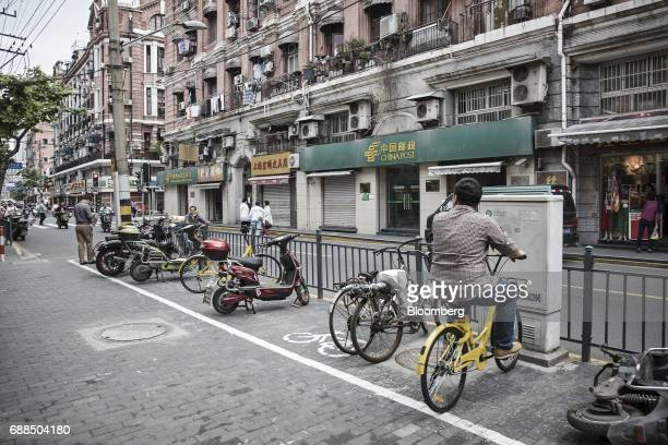 A commuter sits on an Ofo Inc bicycle along a sidewalk in Shanghai China on Thursday May 25 2017 In China abicyclesharingphenomenon is changing the...