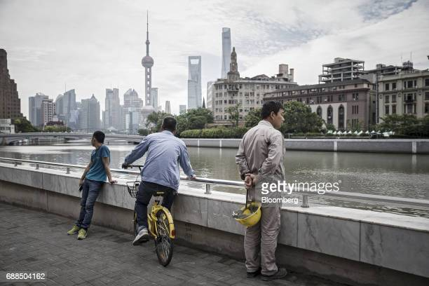 A commuter sits on an Ofo Inc bicycle on a sidewalk in Shanghai China on Thursday May 25 2017 In China abicyclesharingphenomenon is changing the...