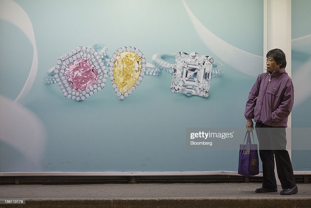 A commuter stands in front of an advertisement for Tiffany & Co. jewelry at a tram stop in Hong Kong, China, on Friday, Jan. 4, 2013. Chief Executive Leung Chun-ying, who has been buffeted by student protests and low popularity since taking office on July 1, has pledged to tackle Asia's biggest wealth gap as the division between poor and rich widened to its worst level since at least 1971. Photographer: Jerome Favre/Bloomberg via Getty Images
