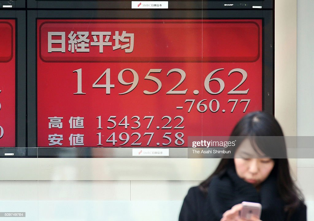 A commuter stands in front of an electric board displaying the Nikkei index on February 12, 2016 in Tokyo, Japan. Japan's Nikkei 225 index continues to drop, below 15,000 points, first time in 16 month amid the Japanese Yen soaring and uncertainty of the global economy.