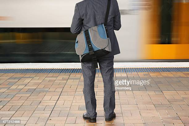 A commuter stands on a platform as a train travels past at Central Station in Sydney Australia on Tuesday June 9 2015 Australian wages fell in the...