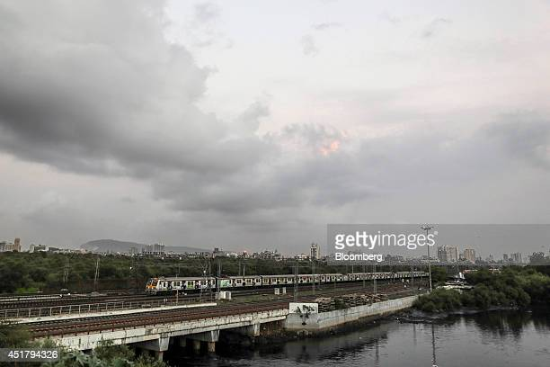 A commuter train passes over Mahim Creek en route to the suburbs during the evening rush hour in Mumbai India on Saturday July 5 2014 Indian...