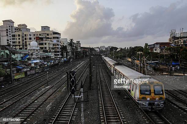 A commuter train travels along a track near Bandra railway station in Mumbai India on Friday July 4 2014 Indian Railways' annual budget is scheduled...