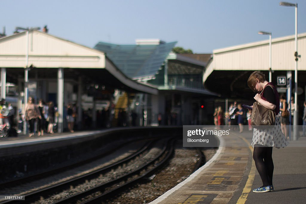 A commuter uses a mobile device as she waits on a platform for a passenger train at Clapham Junction station in London, U.K., on Tuesday, July 9, 2013. U.K. Prime Minister David Cameron is committed to the building of a high-speed rail line linking London to northern England, his spokesman said as evidence mounts that all-party support for the project is fracturing. Photographer: Simon Dawson/Bloomberg via Getty Images