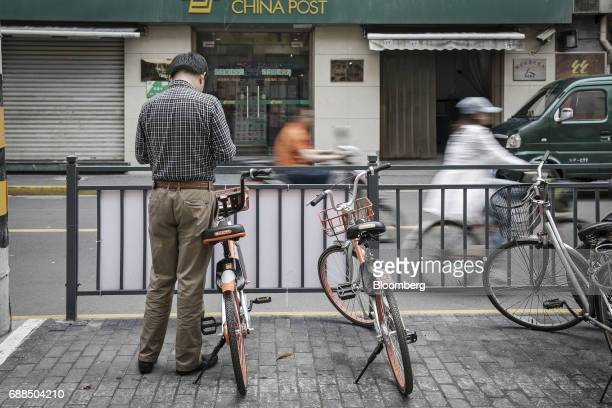 A commuter uses a smartphone next to a Mobike bicycle on a sidewalk in Shanghai China on Thursday May 25 2017 In China a bicyclesharing phenomenon is...