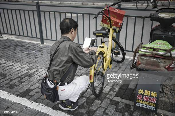 A commuter uses a smartphone to scan a QR code on an Ofo Inc bicycle on a sidewalk in Shanghai China on Thursday May 25 2017 In China...