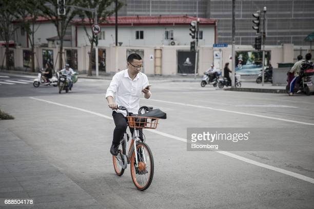 A commuter uses a smartphone while riding a Mobike bicycle along a street in Shanghai China on Thursday May 25 2017 In China...