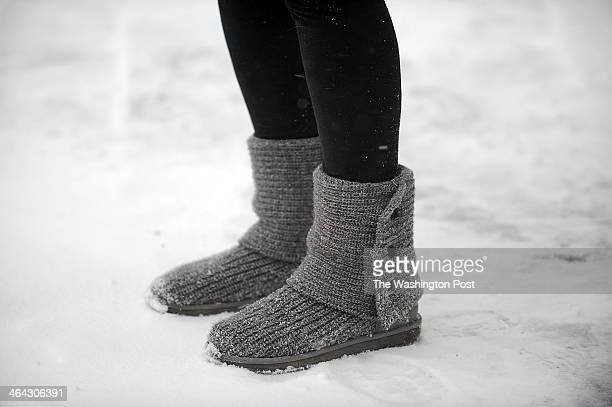 A commuter waiting at a bus stop wears UGG winter boots to withstand a winter storm with a predicted snow accumulation of up to 7 inch in the...
