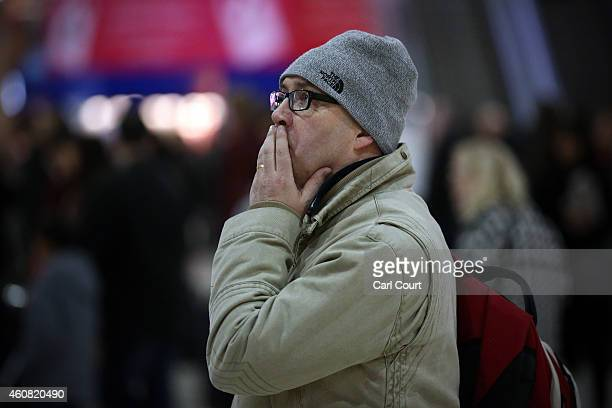 A commuter waits for a train at Waterloo Station on December 24 2014 in London England Although London buses run 24 hours a day throughout the...