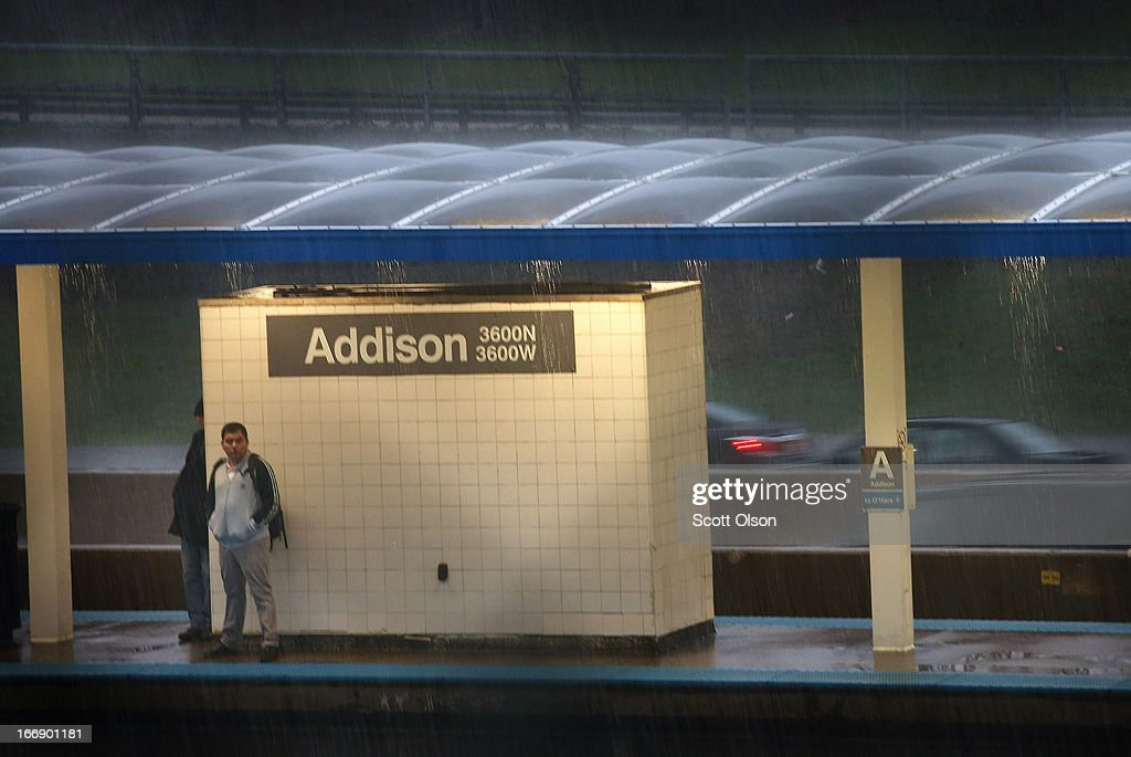 A commuter waits in the rain for a L train on a platform near downtown on April 18, 2013 in Chicago, Illinois. Thunderstorms dumped up to 5 inches of rain on parts of the Chicago area overnight, closing sections the Edens, Eisenhower and Kennedy expressways, which lead to and from downtown, during the morning rush.