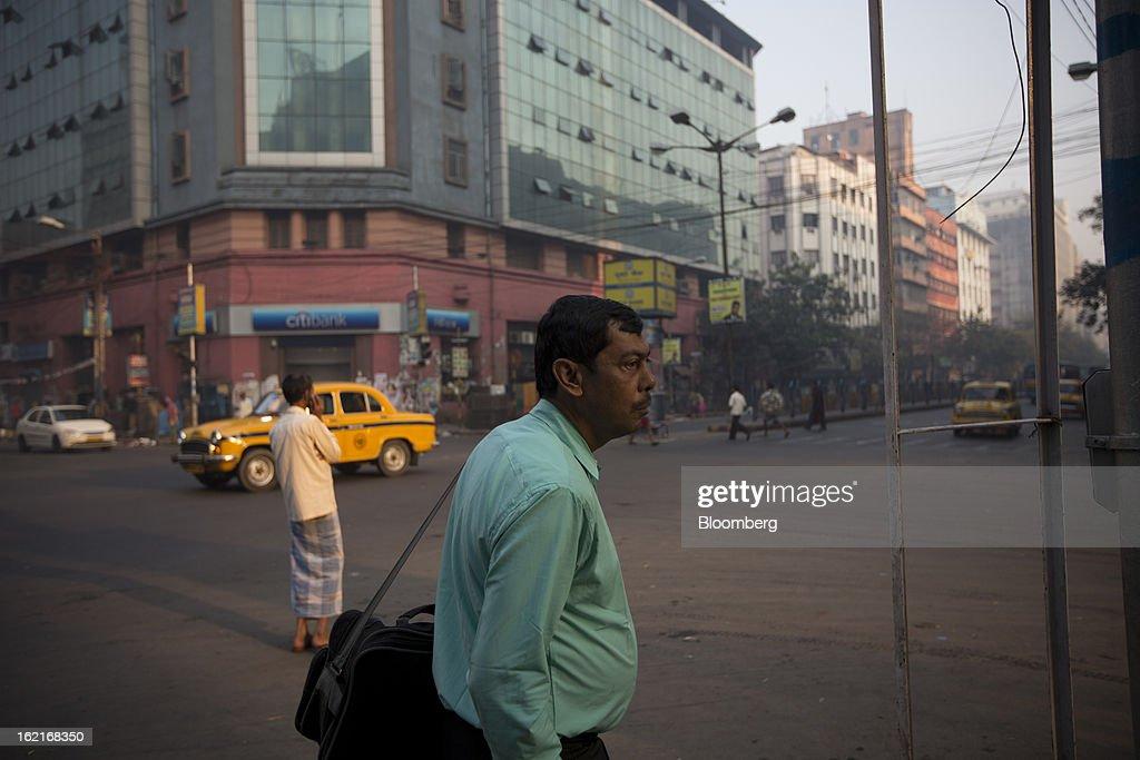 A commuter waits to cross a street in Kolkata, India, on Tuesday, Feb. 19, 2013. India's slowest economic expansion in a decade is limiting profit growth at the biggest companies even as foreigners remain net buyers of the nation's stocks, according to Kotak Institutional Equities. Photographer: Brent Lewin/Bloomberg via Getty Images