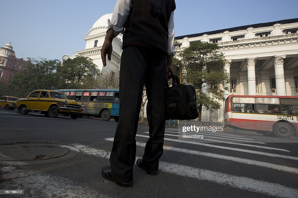 A commuter waits to cross a street in the BBD Bagh area of Kolkata, India, on Tuesday, Feb. 19, 2013. India's slowest economic expansion in a decade is limiting profit growth at the biggest companies even as foreigners remain net buyers of the nation's stocks, according to Kotak Institutional Equities. Photographer: Brent Lewin/Bloomberg via Getty Images