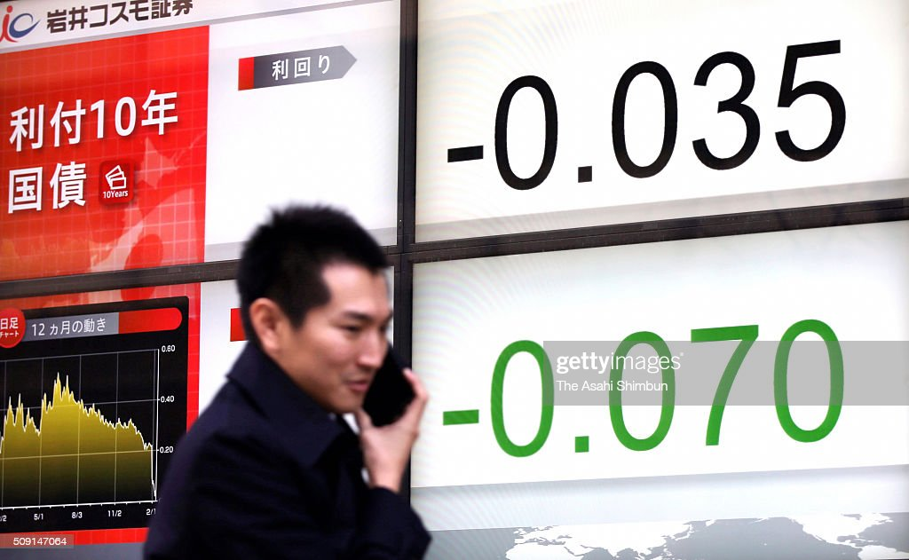 A commuter walk past an electric board displaying the yield of the Japanese government's 10-year bond turns negative for the first time on February 9, 2016 in Tokyo, Japan. The Bank of Japan have decided that, beginning February 16, it will apply an interest rate of minus 0.1 percent to some reserves that financial institutions have at the BOJ.