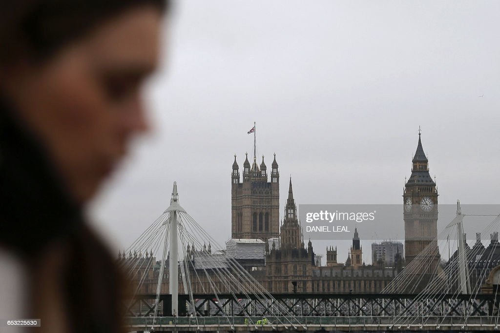 A commuter walks across Waterloo Bridge, backdropped by The Elizabeth Tower, better known as 'Big Ben', and the Houses of Parliament, in central London on March 14, 2017. Prime Minister Theresa May is set to begin the countdown to Brexit after parliament gave her the green light -- and Scotland wrong-footed her by launching a fresh bid for independence. Downing Street has played down speculation that May could announce Tuesday that she is triggering the Article 50 process to leave the European Union, indicating that it would take place later in the month. / AFP PHOTO / Daniel LEAL