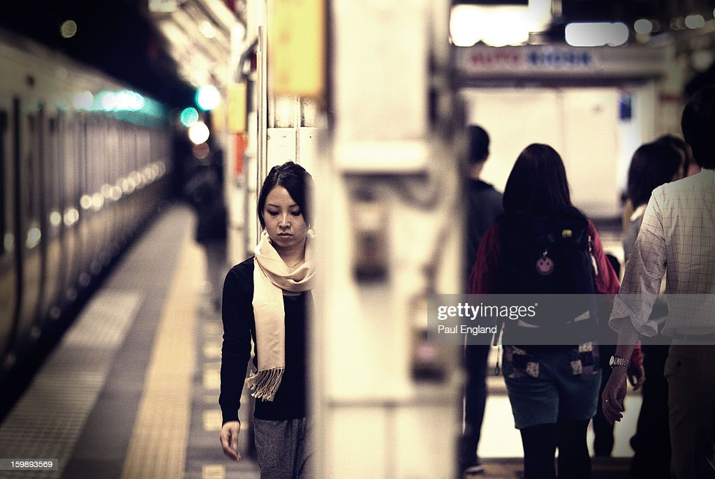 CONTENT] A commuter walks on the platform one evening in a Tokyo train station.