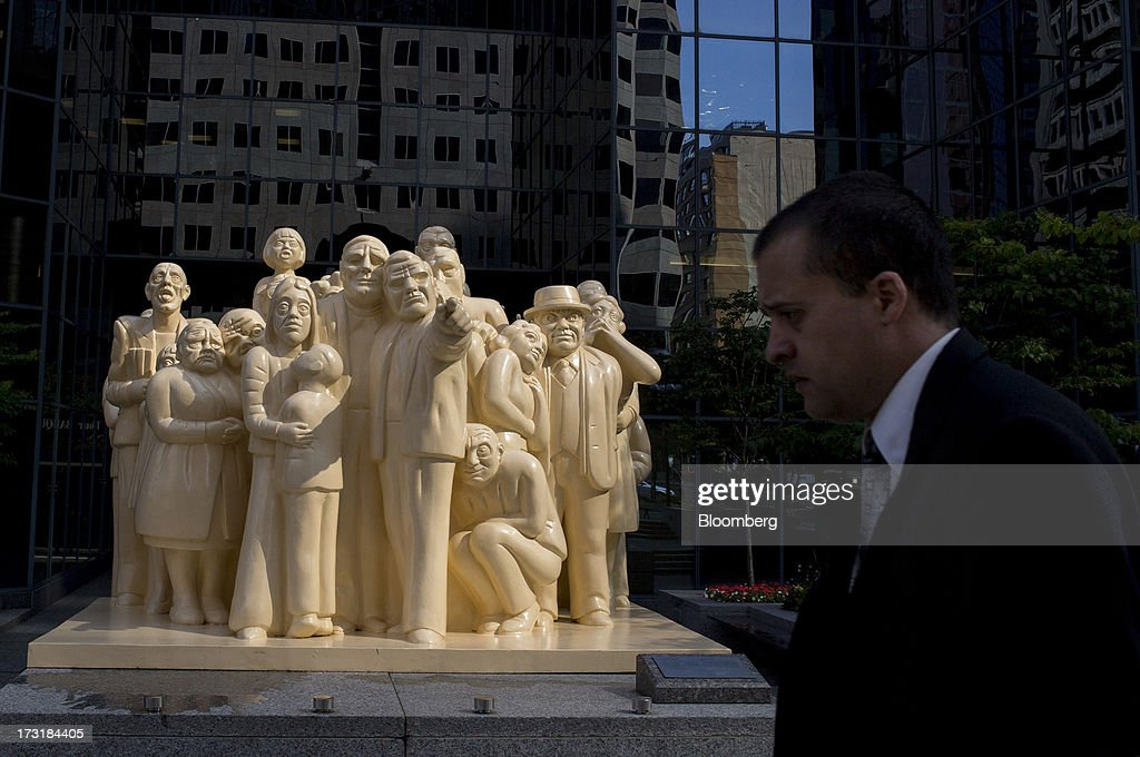 A commuter walks past a statue in Montreal, Quebec, Canada, on Monday, July 8, 2013. Montreals city council elected Laurent Blanchard as interim mayor to replace Michael Applebaum, who quit last week after being arrested on corruption charges. Photographer: Brent Lewin/Bloomberg via Getty Images