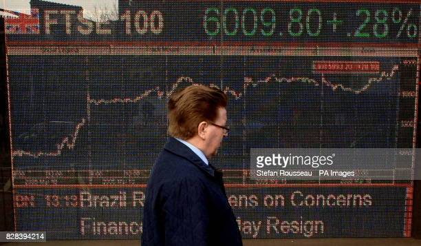 A commuter walks past an electronic display showing the FTSE index at the milestone of 600980 Friday March 17 which it hit today for the first time...