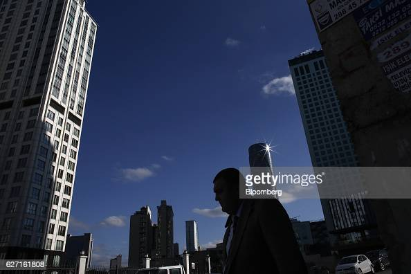 A commuter walks past commercial buildings in the business district of Maslak in Istanbul Turkey on Thursday Dec 1 2016 The lira has plummeted after...