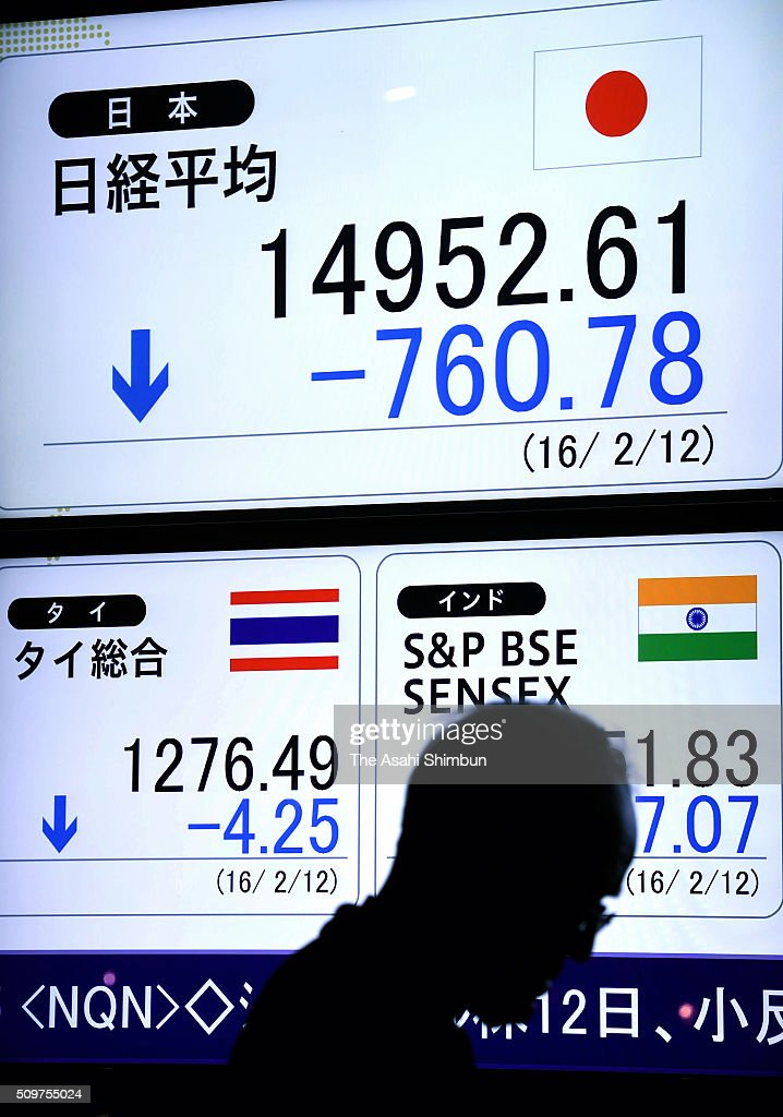 A commuter walks past in front of an electric board displaying the Nikkei index on February 12, 2016 in Tokyo, Japan. Japan's Nikkei 225 index continues to drop, below 15,000 points, first time in 16 month amid the Japanese Yen soaring and uncertainty of the global economy.