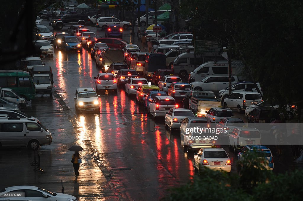 A commuter walks under monsoon rain while vehicles wait at a traffic light during rush hour in Yangon on May 26, 2016. / AFP / ROMEO