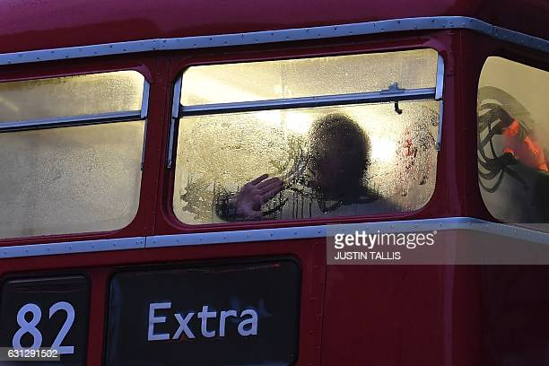 A commuter wipes condensation from the window of an extra bus s put on to help with capacity during a 24hour tube strike near to Victoria station in...