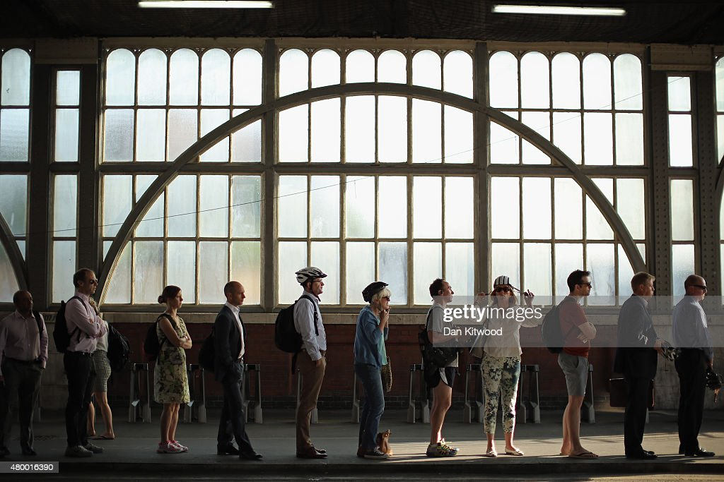 Commuters adjust their helmets as they queue at a bike hire point at Waterloo Station on July 9 2015 in London England London Underground workers are...