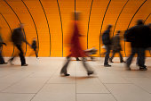 XXXL - motion blurred commuters in different size against modern orange subway tube in background - tiled floor in foreground - camera canon 5D mark II - unsharped RAW - adobe colorspace