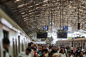 Commuters and passengers walk past trains sitting at railway platforms at Churchgate railway station in Mumbai India on Saturday Feb 21 2015 Indian...