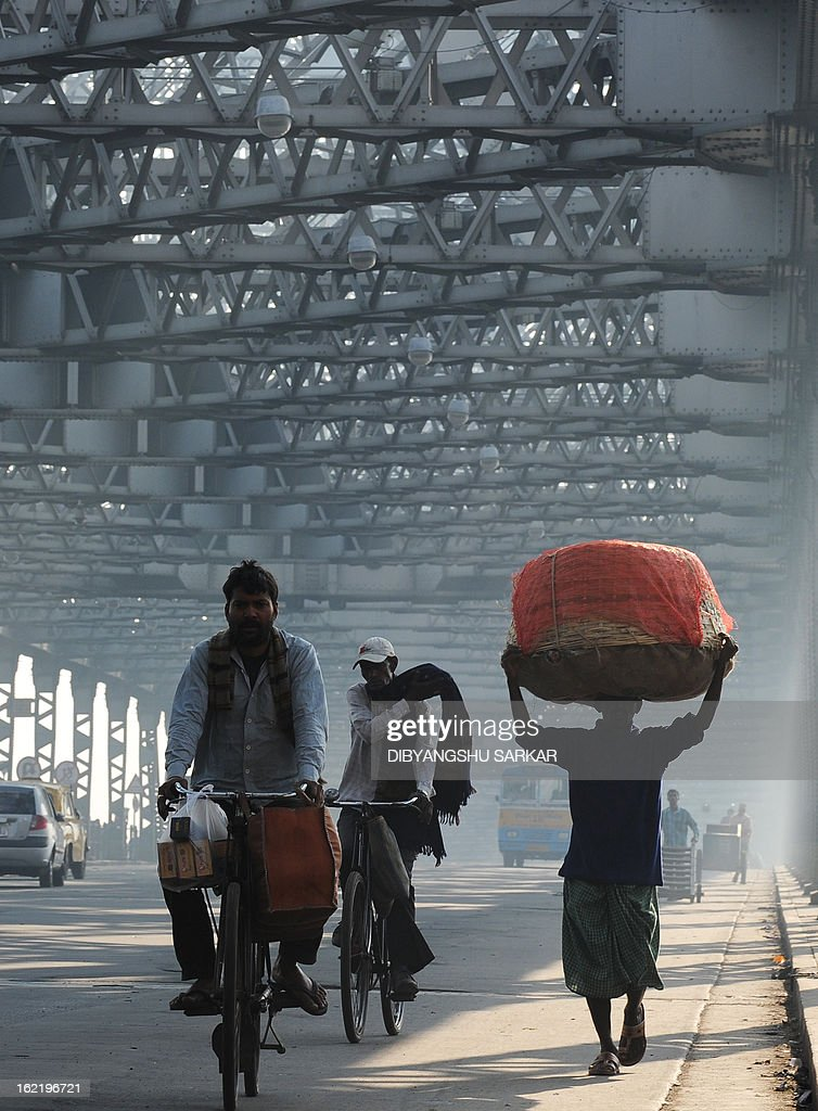 Commuters and pedestrian make their way across the Howrah bridge during a two-day strike opposing the current UPA government's economic policies in Kolkata on February 20, 2013. Millions of India's workers walked off their jobs in a two-day nationwide strike called by trade unions to protest at the 'anti-labour' policies of the embattled government. Financial services and transport were hit by the strike called by 11 major workers' groups to protest at a series of pro-market economic reforms announced by the government last year, as well as high inflation and rising fuel prices. AFP PHOTO/Dibyangshu SARKAR