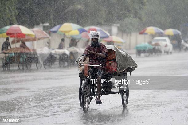 Commuters and pedestrians look on road as they moves past wade throw in the torrential rain in the eastern Indian city Bhubaneswar India Tuesday 02...