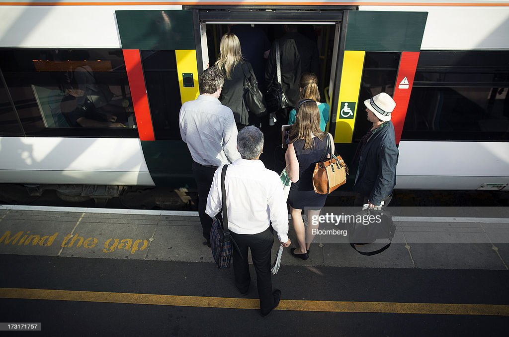 Commuters and rail travelers board a rush hour passenger train before departing from Clapham Junction station in London, U.K., on Tuesday, July 9, 2013. U.K. Prime Minister David Cameron is committed to the building of a high-speed rail line linking London to northern England, his spokesman said as evidence mounts that all-party support for the project is fracturing. Photographer: Simon Dawson/Bloomberg via Getty Images