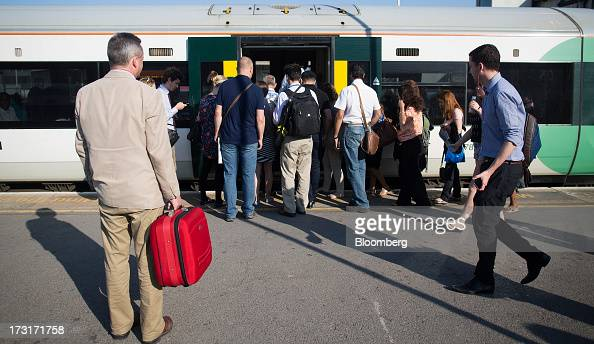 Commuters and rail travelers board a rush hour passenger train operated by Southern Railway Ltd before departing from Clapham Junction station in...