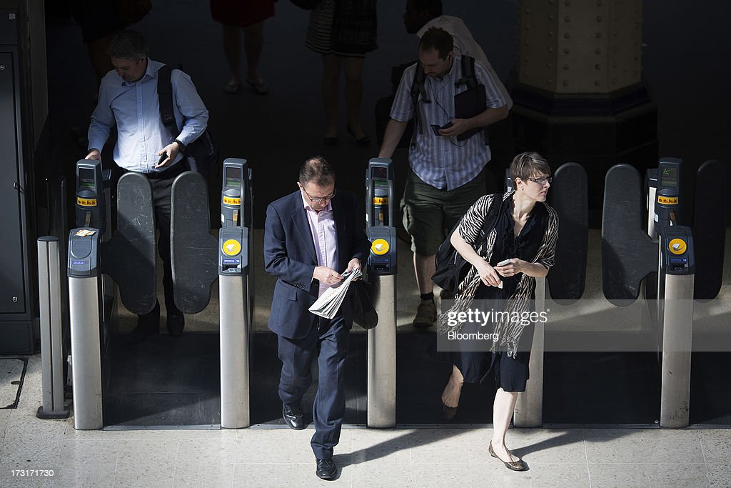 Commuters and rail travelers pass through the ticket gates after arriving by passenger train at Waterloo station in London, U.K., on Tuesday, July 9, 2013. U.K. Prime Minister David Cameron is committed to the building of a high-speed rail line linking London to northern England, his spokesman said as evidence mounts that all-party support for the project is fracturing. Photographer: Simon Dawson/Bloomberg via Getty Images