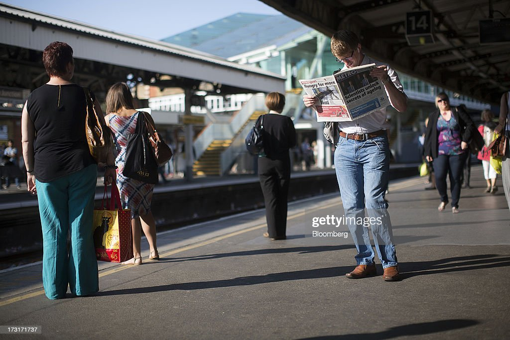 Commuters and rail travelers stand on a platform as they wait for a passenger train to arrive at Clapham Junction station in London, U.K., on Tuesday, July 9, 2013. U.K. Prime Minister David Cameron is committed to the building of a high-speed rail line linking London to northern England, his spokesman said as evidence mounts that all-party support for the project is fracturing. Photographer: Simon Dawson/Bloomberg via Getty Images