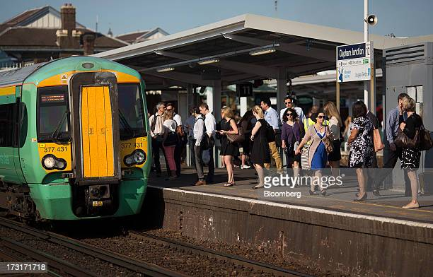 Commuters and rail travelers wait on a platform as a passenger train operated by Southern Railway Ltd approaches at Clapham Junction station in...