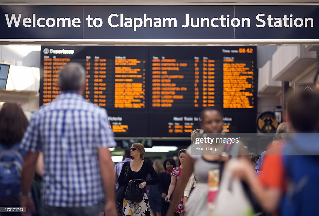 Commuters and rail travelers walk beneath a sign inside Clapham Junction train station in London, U.K., on Tuesday, July 9, 2013. U.K. Prime Minister David Cameron is committed to the building of a high-speed rail line linking London to northern England, his spokesman said as evidence mounts that all-party support for the project is fracturing. Photographer: Simon Dawson/Bloomberg via Getty Images