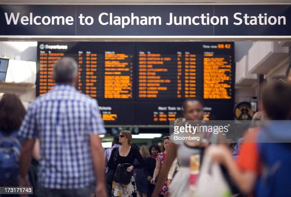 Commuters and rail travelers walk beneath a sign inside Clapham Junction train station in London UK on Tuesday July 9 2013 UK Prime Minister David...