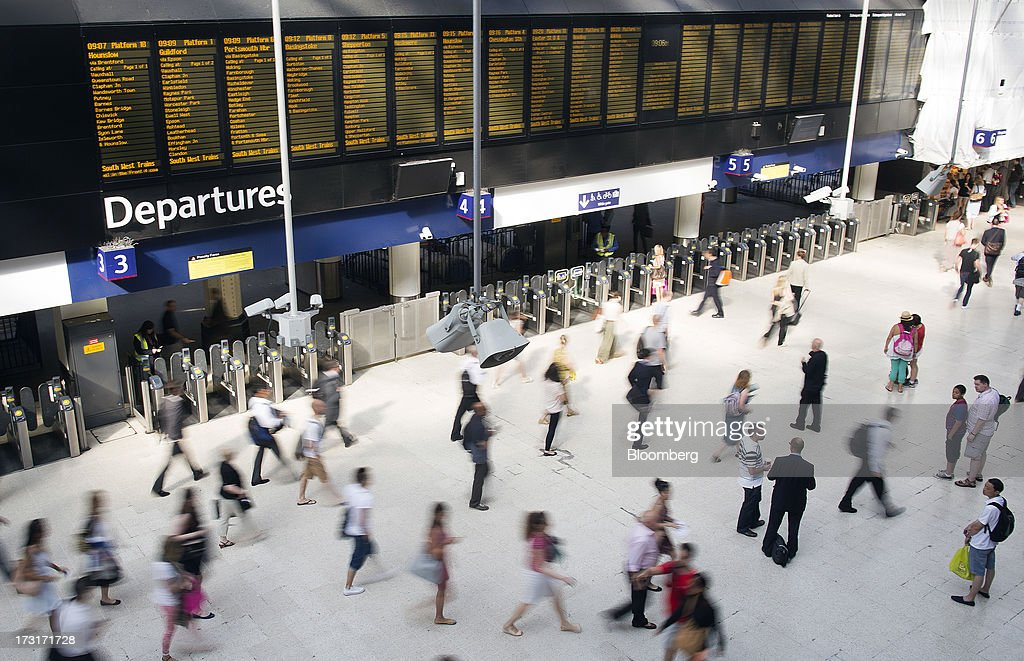 Commuters and rail travelers walk beneath the departures board at Waterloo train station in London, U.K., on Tuesday, July 9, 2013. U.K. Prime Minister David Cameron is committed to the building of a high-speed rail line linking London to northern England, his spokesman said as evidence mounts that all-party support for the project is fracturing. Photographer: Simon Dawson/Bloomberg via Getty Images