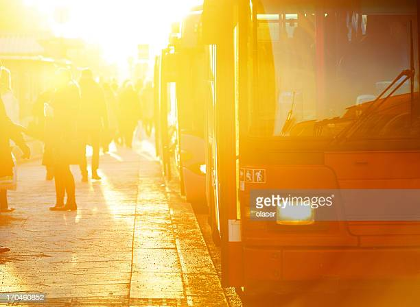 Commuters and red bus in sunset