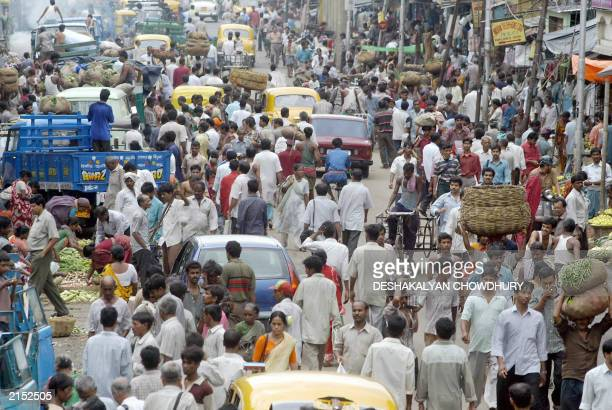 Commuters and shoppers make their way along a crowded street on the eve the world population day in Calcutta 10 July 2003 The United Nations...