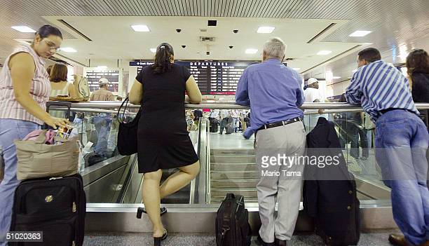 Commuters and travelers wait for their trains in Penn Station July 2 2004 in New York City AAA estimates that 394 millions Americans will travel 50...
