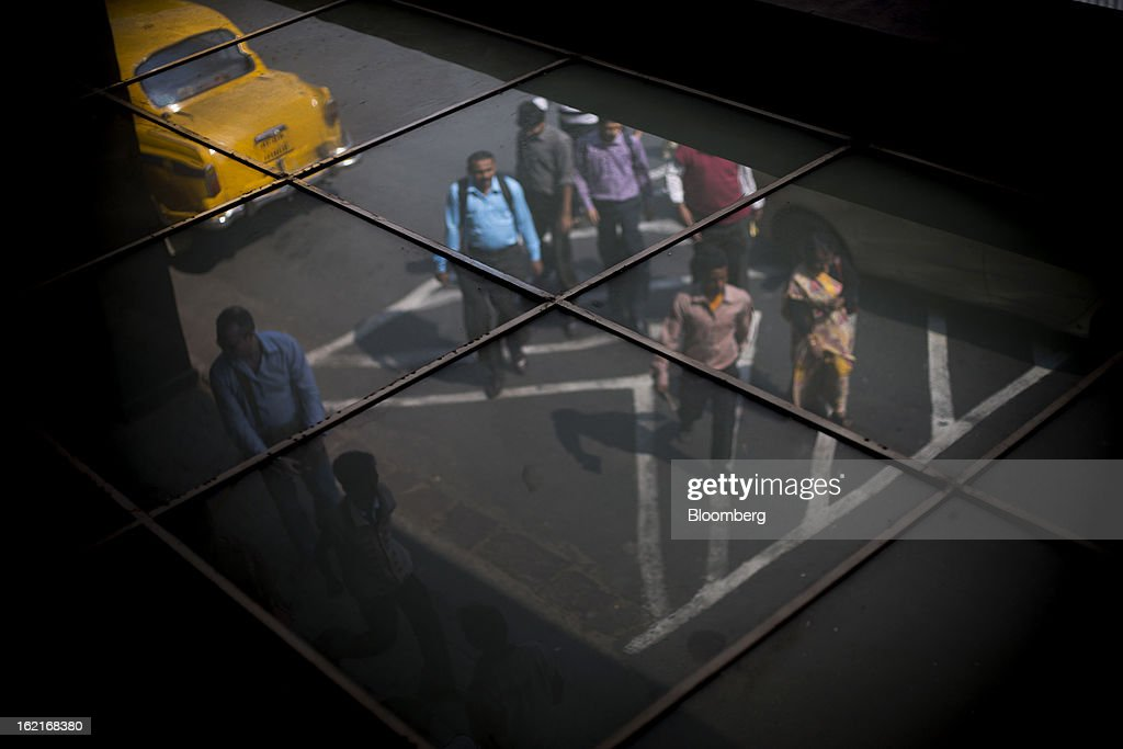 Commuters are reflected in a tiled ceiling in Kolkata, India, on Tuesday, Feb. 19, 2013. India's slowest economic expansion in a decade is limiting profit growth at the biggest companies even as foreigners remain net buyers of the nation's stocks, according to Kotak Institutional Equities. Photographer: Brent Lewin/Bloomberg via Getty Images