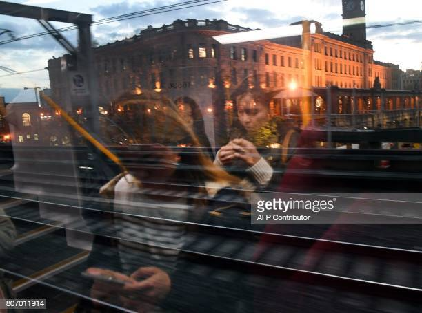 Commuters are reflected in the window glass as they study their mobile phones while travelling home past Sydney's Central Station on July 4 2017...