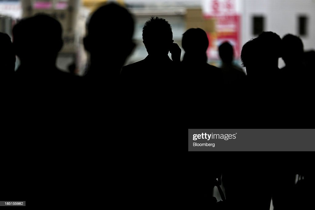 Commuters are silhouetted as they walk along a street in Tokyo, Japan, on Thursday, Oct. 17, 2013. Asian stocks rose, sending the benchmark index to a five-month high, while the regions bond risk fell and emerging-market currencies strengthened after U.S. lawmakers voted to raise the nations debt limit. Photographer: Kiyoshi Ota/Bloomberg via Getty Images