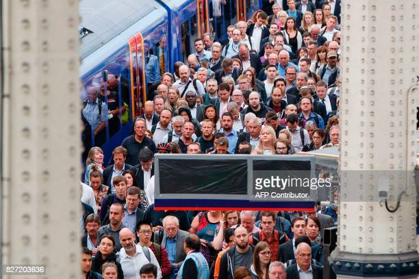 Commuters are ushered off of a train as they arrive at London Waterloo rail station in central London on August 7 as Network Rail commences major...