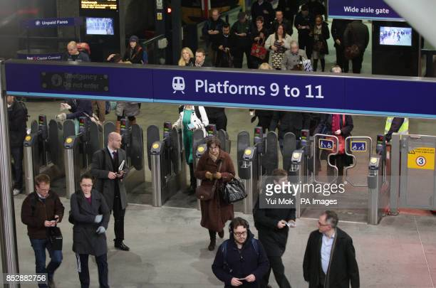 Commuters arriving through the ticket barriers at Kings Cross Station in London on the day that new train fares come into force