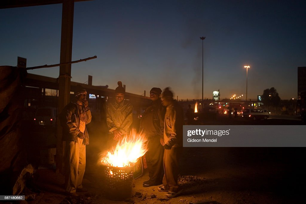 Commuters at the Baragwanath taxi rank warm themselves with the flames on a hawkers brazier on a cold winter morning When the fire has burnt down the...