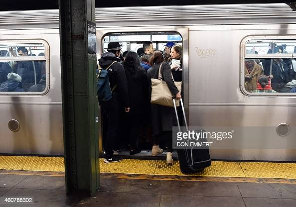 Commuters at the Bedford Ave subway station board a crowded train December 22 2014 in New York The last stop that the L train makes before traveling...