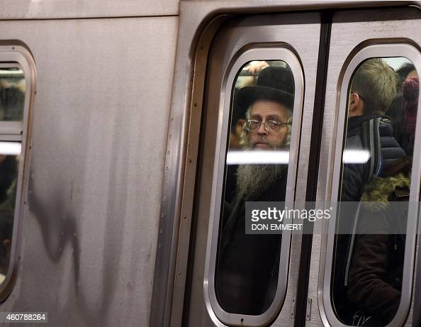 Commuters at the Bedford Ave subway station on board a crowded train December 22 2014 in New York The last stop that the L train makes before...