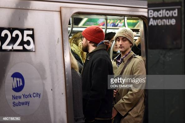 Commuters at the Bedford Ave subway station onboard a crowded train December 22 2014 in New York The last stop that the L train makes before...